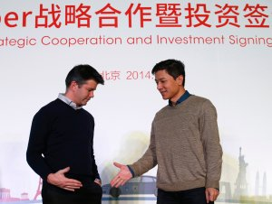 Baidu Inc. Chairman and CEO Li reaches out to shake hands with Uber CEO Kalanick during the Baidu and Uber strategic cooperation and investment signing ceremony in Beijing